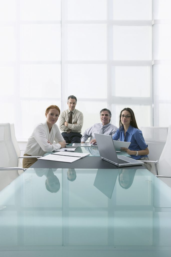 Group of Businesspeople Sitting at Conference Table --- Image by © Larry Williams & Associates/zefa/Corbis